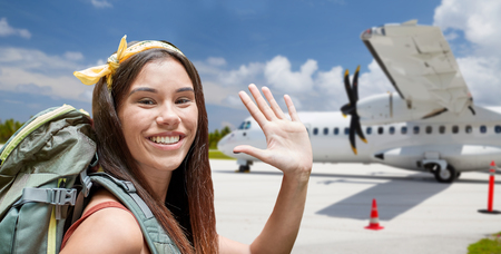 air travel, tourism and trip concept - smiling tourist woman with backpack over plane on airfield background