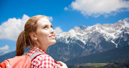 adventure, travel, tourism, hike and people concept - smiling young woman with backpack over alps mountains background
