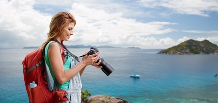 travel, tourism and photography concept - happy young woman with backpack and camera over background of seychelles island in indian ocean
