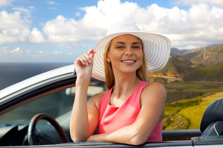 travel, road trip and people concept - happy young woman wearing sun hat in convertible car over bixby creek bridge on big sur coast of california background Stock Photo