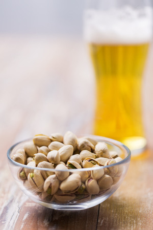 food and drinks concept - pistachio nuts in bowl and glass of draught beer