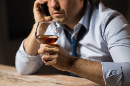 alcoholism, alcohol addiction and people concept - close up of male alcoholic drinking brandy and calling on smartphone at night Stock Photo - 101831821