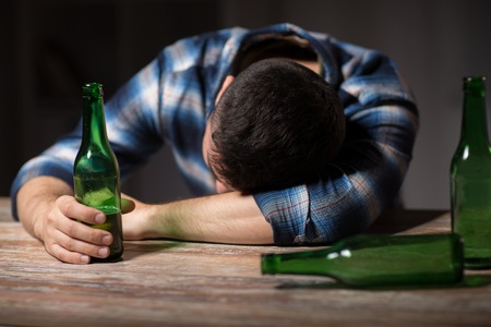 alcoholism, alcohol addiction and people concept - male alcoholic with beer bottles lying or sleeping on table at night