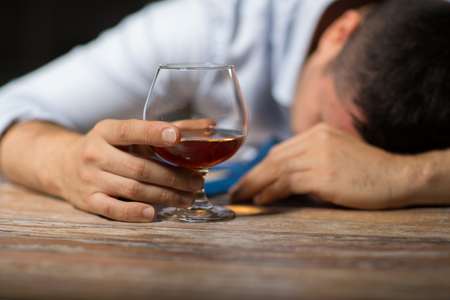 alcoholism, alcohol addiction and people concept - male alcoholic with glass of brandy lying or sleeping on table at night