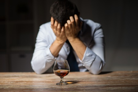 drunk man with glass of alcohol on table at night