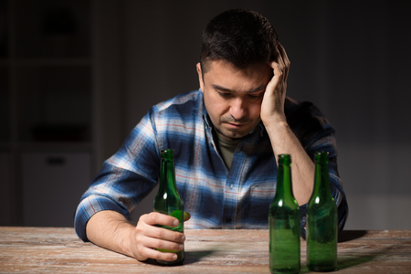 alcoholism, alcohol addiction and people concept - male alcoholic with bottles drinking beer at table at night