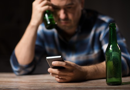 alcoholism, alcohol addiction and people concept - drunk man with smartphone and bottle of beer at night Banque d'images - 101831842