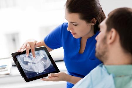dentista y paciente con rayos x de dientes en tablet pc