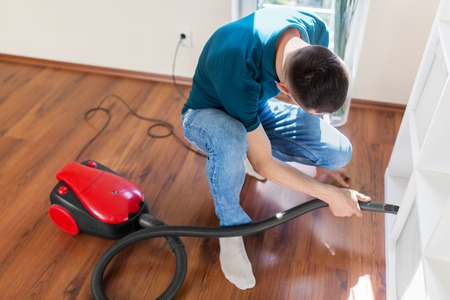 man with vacuum cleaner at home Stock Photo