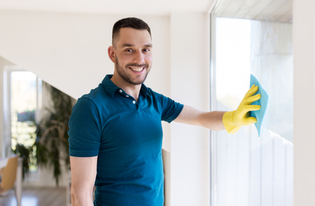 man in rubber gloves cleaning window with rag
