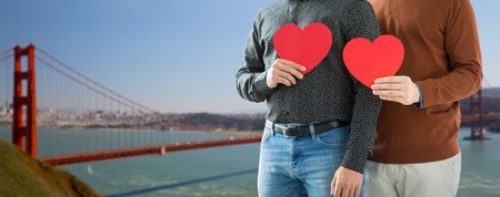 close up of happy male couple holding red hearts Stock Photo