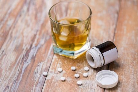 Glas Alkohol und Pillen auf dem Tisch
