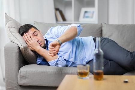 Alkoholiker, der auf dem Sofa liegt und Armbanduhr betrachtet