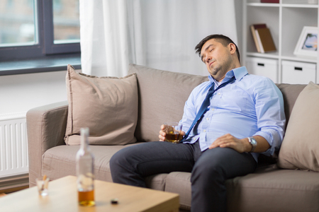 drunk man with glass of alcohol sleeping at home Stock Photo