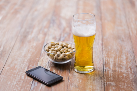 glass of beer, smartphone and pistachio on table 스톡 콘텐츠