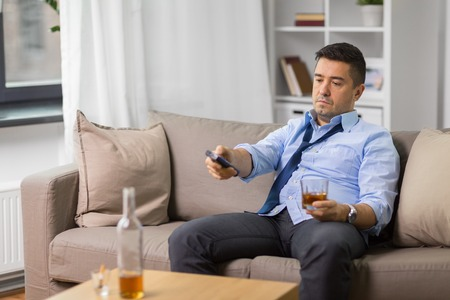 drunk man with tv remote drinking alcohol at home Stock Photo