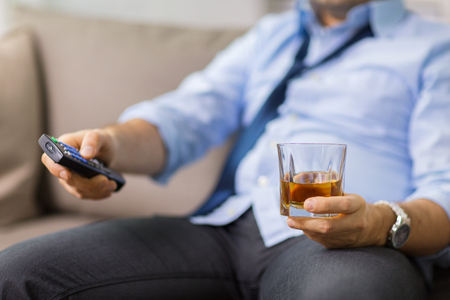 close up of man with tv remote drinking alcohol Stock Photo