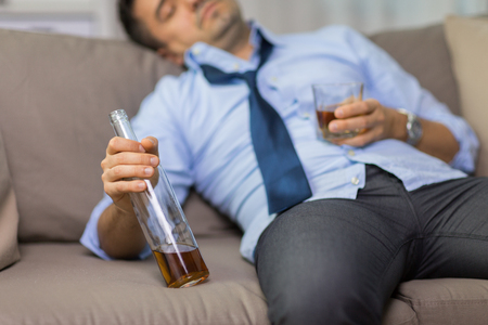 close up of man sleeping with bottle of alcohol Stock Photo