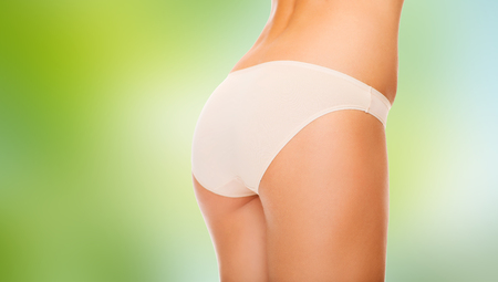 beauty and slimming concept - close up of woman body in cotton underwear over green natural background Stock Photo