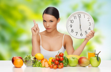 diet, healthy eating and people concept - woman with food and clock showing six warning over green natural background
