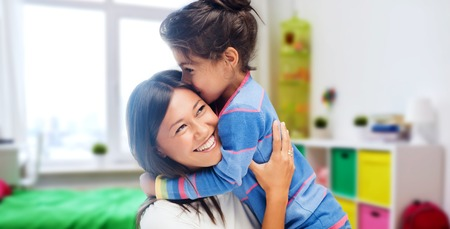family, motherhood and people concept - happy mother and daughter hugging and kissing over kids room at home background Standard-Bild