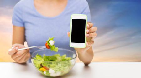 healthy eating, technology, food and people concept - close up of young woman with smartphone and vegetable salad over sky background Stock Photo