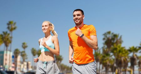 fitness, sport and healthy lifestyle concept - smiling couple with heart-rate watch running over venice beach background in california