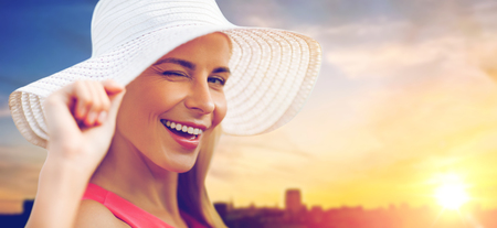 summer, fashion and people concept - portrait of beautiful smiling woman in sun hat over city sunset background 版權商用圖片 - 102601260