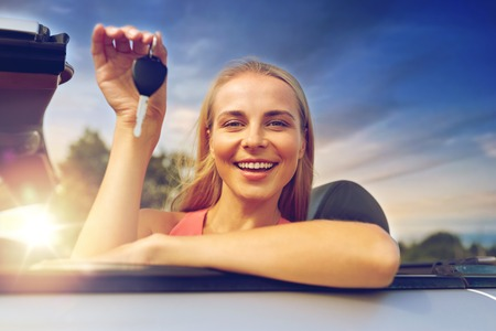 movable property, security and transport concept - happy young woman with convertible car key over evening sky background