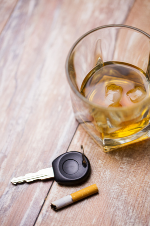 alcohol abuse, drunk driving and people concept - close up of whiskey glass and car key on table Stock Photo