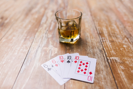 gambling, fortune and entertainment concept - glass of whisky and playing cards on table Stock Photo