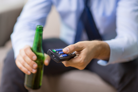 alcoholism, alcohol addiction and people concept - close up of man with tv remote drinking beer Banco de Imagens