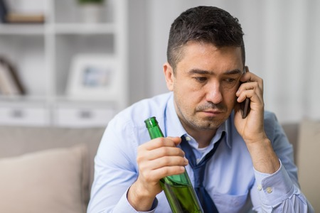 alcoholism, alcohol addiction and people concept - male alcoholic drinking beer and calling on smartphone at home
