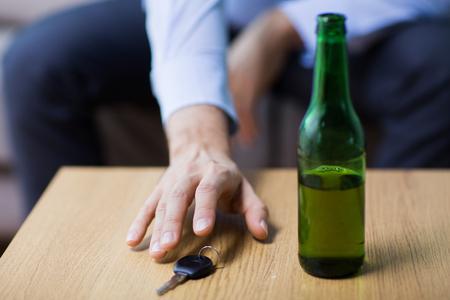 nadużywanie alkoholu, jazda po pijanemu i koncepcja ludzi - zbliżenie butelki piwa i męskiej ręki kierowcy biorąc kluczyk ze stołu Zdjęcie Seryjne