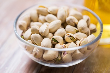 food concept - close up of pistachio nuts in glass bowl