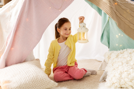 childhood and hygge concept - happy little girl with christmas lantern in kids tent at home Banco de Imagens