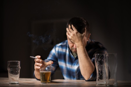 alcoholism, alcohol addiction and people concept - male alcoholic drinking beer and smoking cigarette at night