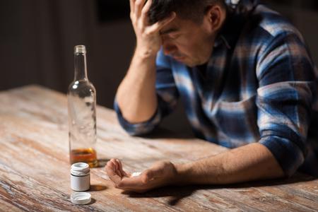 koncepcja depresji, narkomanii i uzależnień - nieszczęśliwy pijany mężczyzna z butelką alkoholu i pigułkami popełnia samobójstwo przez przedawkowanie leków w nocy Zdjęcie Seryjne