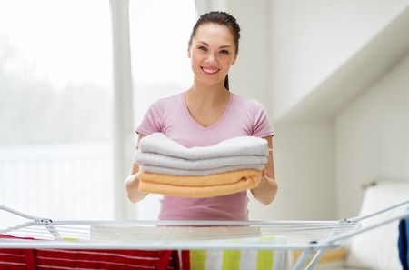 woman with bath towels and drying rack at home