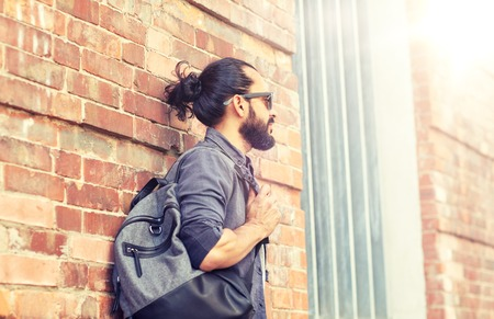 man with backpack standing at city street wall Stock Photo