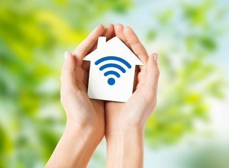 manos sosteniendo la casa con el icono de señal de ondas de radio Foto de archivo