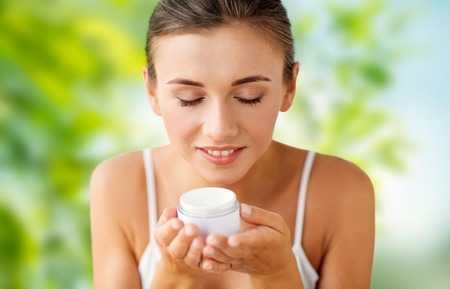 close up of happy woman holding and smelling cream Stock Photo