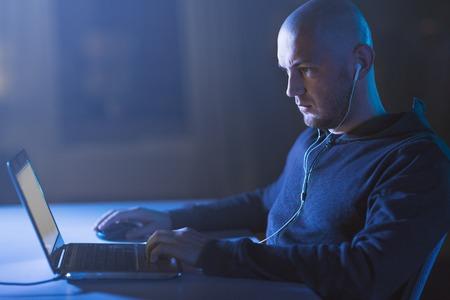 hacker in earphones typing on laptop in dark room