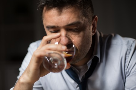 close up of drunk man drinking alcohol at night