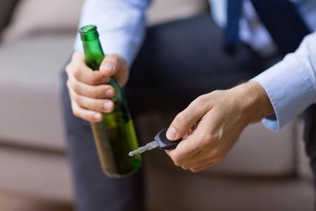männliche Fahrerhände, die Bierflasche und Autoschlüssel halten