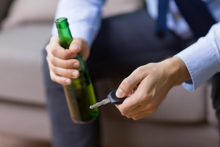 male driver hands holding beer bottle and car key Stock Photo - 102981560