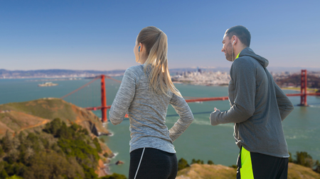 couple with earphones running over san francisco Stock Photo