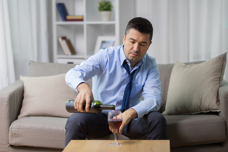 alcoholic pouring red wine to glass at home Stock Photo