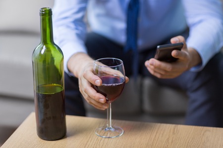 close up of man with alcohol and smartphone