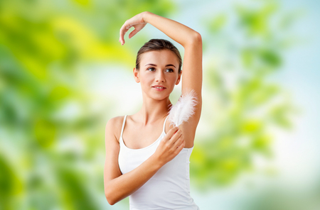 beautiful woman touching her armpit by feather